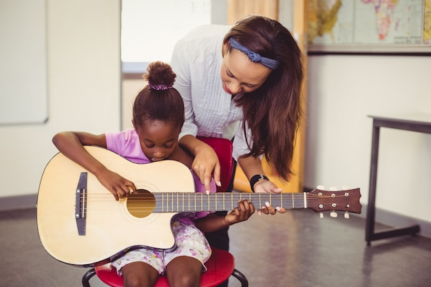 Teacher assisting a girl to play a guitar in classroom