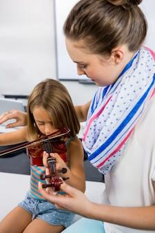 先生が教室でバイオリンホワイトボードを演奏する女の子を支援