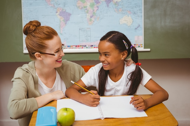 Teacher assisting girl with homework in classroom