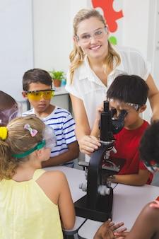 先生が実験室で子供たちを支援