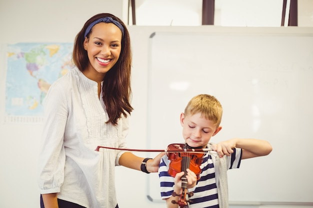 Teacher assisting a schoolboy to play a violin in classroom