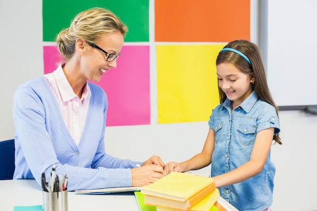 Teacher assisting schoolgirl in drawing