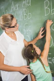 Teacher assisting schoolgirl to learn alphabet on chalkboard in classroom