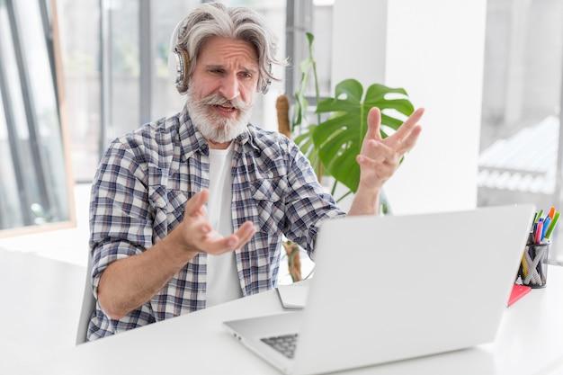 Учитель за столом разговаривает с ноутбуком