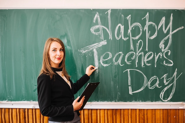 Teacher at blackboard with inscription