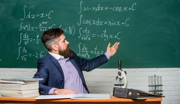 教師のカリスマ的なヒップスターは、テーブルの教室の黒板の背景に座っています。教育的な会話。生徒や生徒と話す。学校の先生のコンセプト。あごひげを生やした先生が面白い話をします。