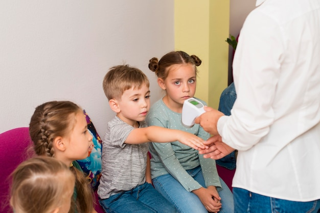 Учитель проверяет температуру своих учеников