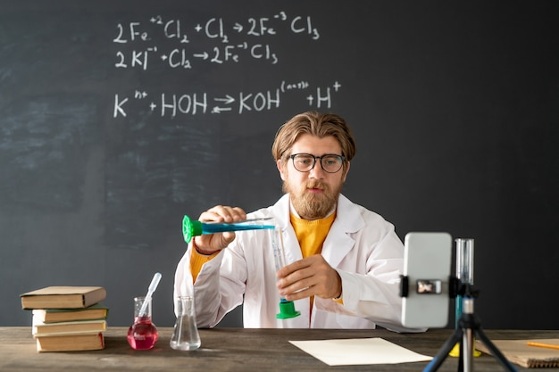 Teacher of chemistry showing chemical reaction while mixing two liquid substances during online lab work in front of smartphone camera