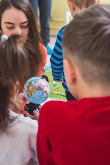 Teacher and children looking globe