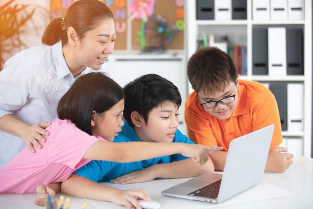 Teacher and cute asian children using laptop computer together.