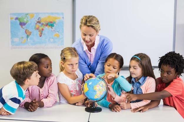 Учитель обсуждает глобус с детьми