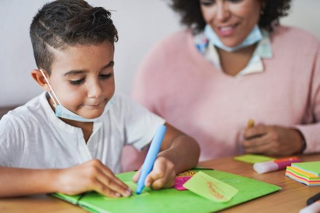 턱 아래에 안전 마스크를 쓰고 소년과 그림 활동을 하는 교사 - 유치원 및 어린이집의 개념