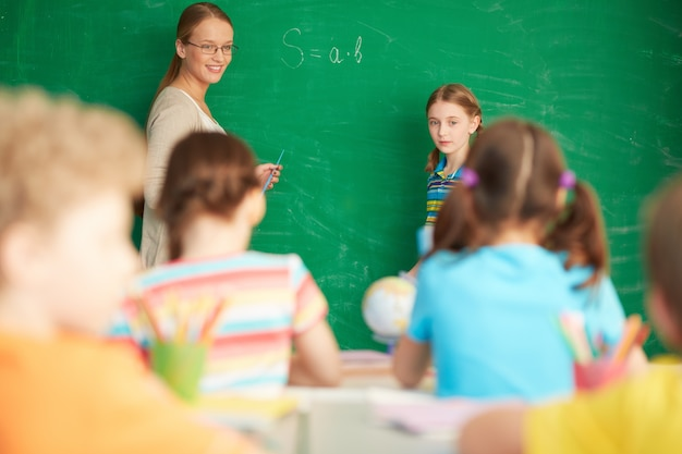 Teacher explaining arithmetic on the blackboard