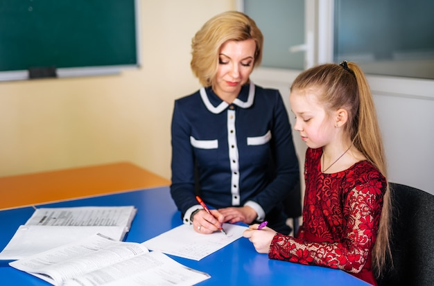 Teacher explaining lesson to a school girl. private lesson at school. tutor and school concept.