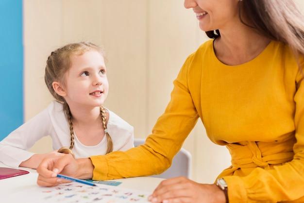 Учитель что-то объясняет маленькой девочке