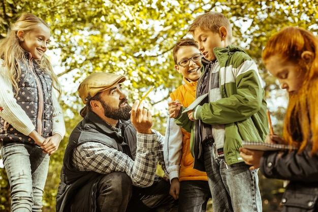 Учитель что-то объясняет своему ученику в лесу в солнечный день