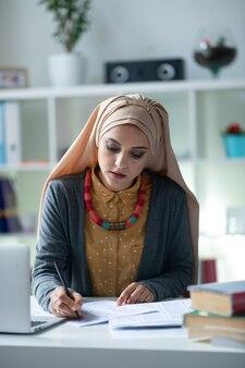 忙しい先生。テストを修正しながら忙しい感じのヒジャーブを身に着けている若い勤勉な教師