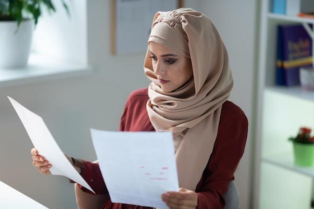 바쁜 선생님. 수업을 준비하는 동안 바쁜 느낌 hijab를 착용하는 젊은 무슬림 교사