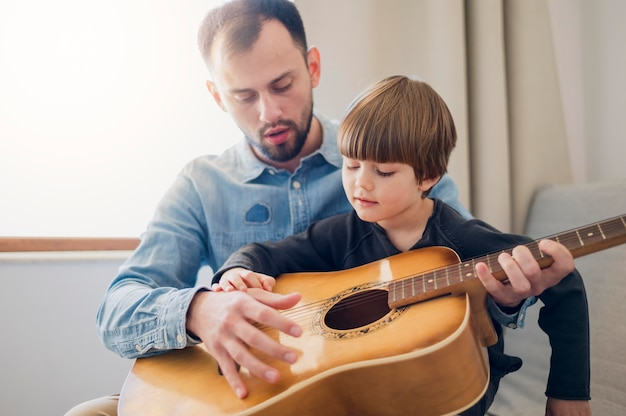 Teacher giving guitar lessons at home to child