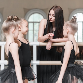 Teacher giving instruction to her ballet girls in dance studio