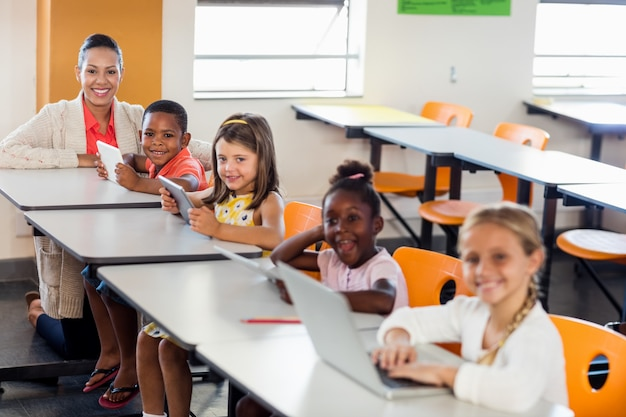 Teacher giving lesson to her students with laptops