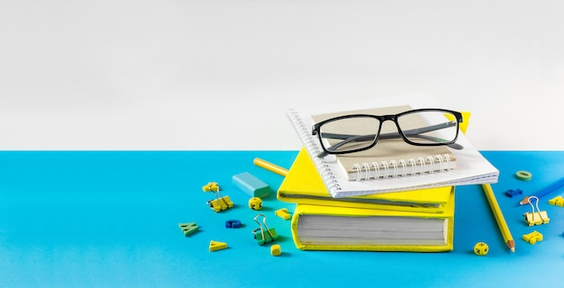 Teacher glasses, books and wooden letters on a blue table. school and teacher day concept. copy space.