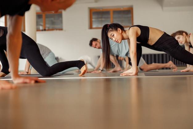 先生はヨガのクラスで生徒を指導します。現代のスポーツクラブでヨガを練習している若いスポーティな人々。