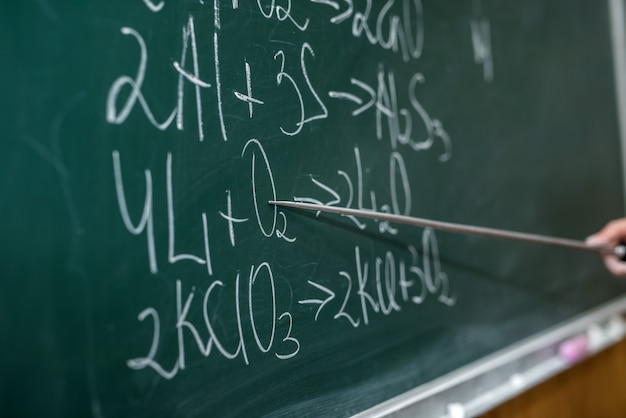 Teacher hand holding pointer and showing formulas in chemistry lesson on blackboard. offline education