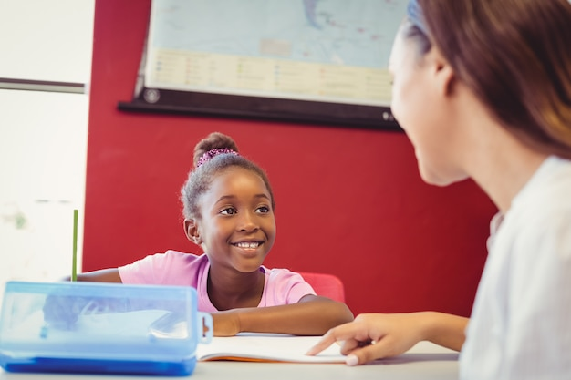 Учитель помогает девочке с домашним заданием в классе