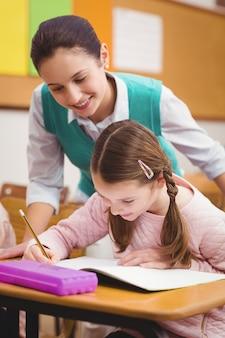 Учитель помогает маленькой девочке во время занятий