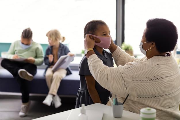 Учитель помогает ученику надеть медицинскую маску