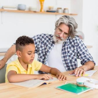 勉強している少年を助ける先生
