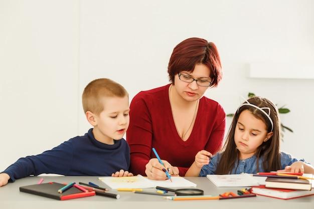 Teacher helping children with homework in classroom at school