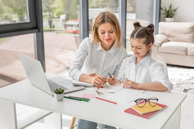 Учитель помогает дочери учиться за столом