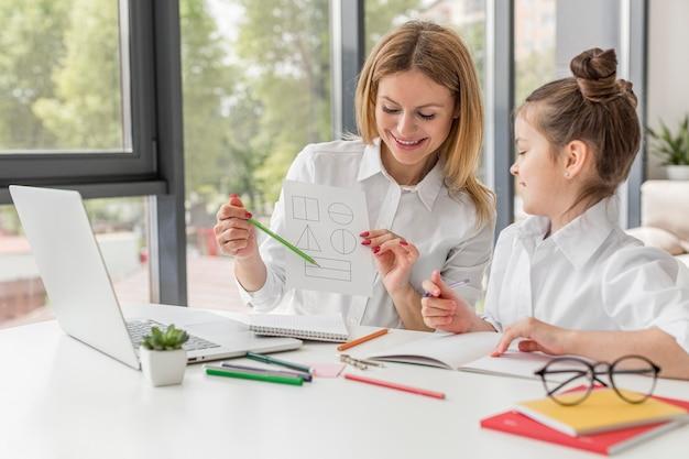 Insegnante che aiuta sua figlia a studiare al chiuso