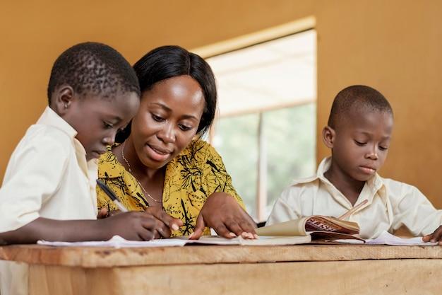 Teacher helping kids in class