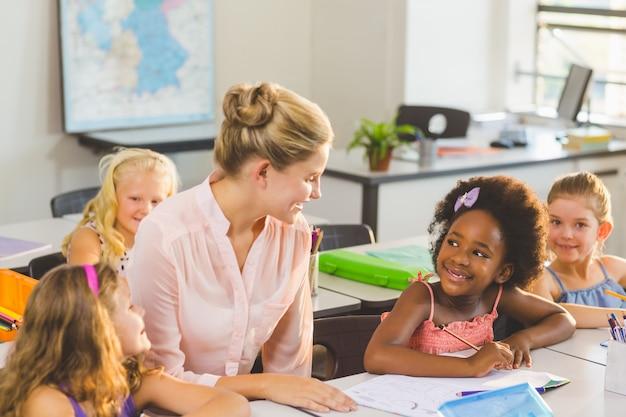Учитель помогает детям с домашней работой в классе