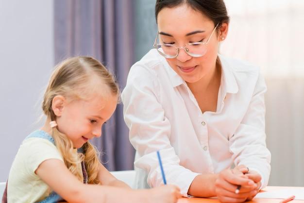 Учитель помогает маленькой девочке в классе