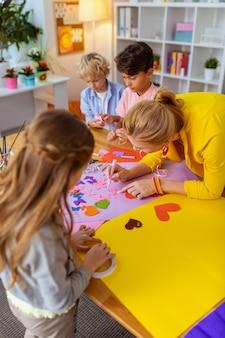 生徒を助ける先生。金髪の若い先生が生徒の絵を描いたり切り抜きを作ったりするのを手伝っています