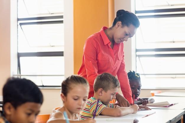 A teacher helping pupils in classroom