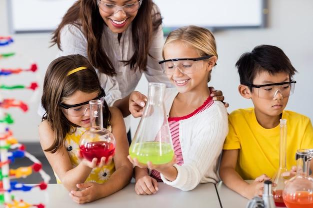 Teacher helping pupils doing science
