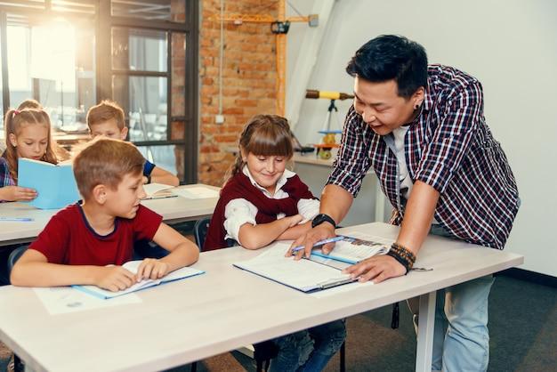 小学校の教室でのテストタスクで学校の子供たちを助ける教師。