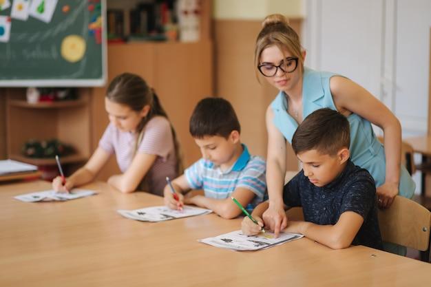 교실에서 시험을 작성하는 학교 아이들을 돕는 교사. 교육, 초등학교, 학습 및