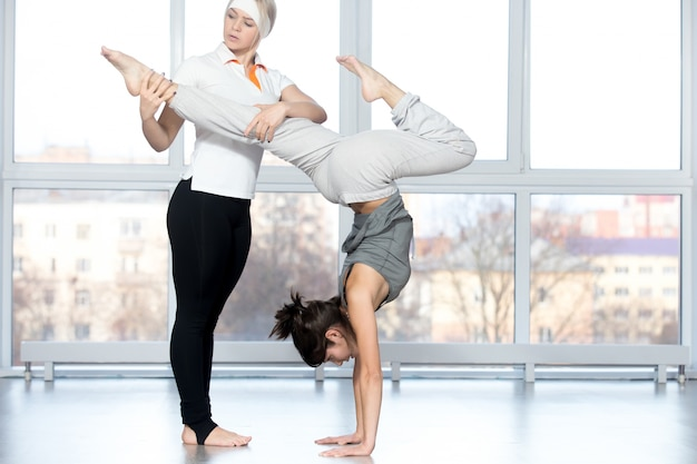 Teacher helping student to do stag handstand