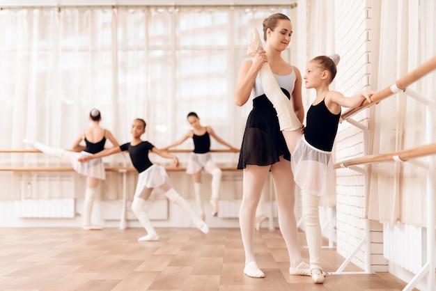 Teacher helps young ballerina near ballet bar.