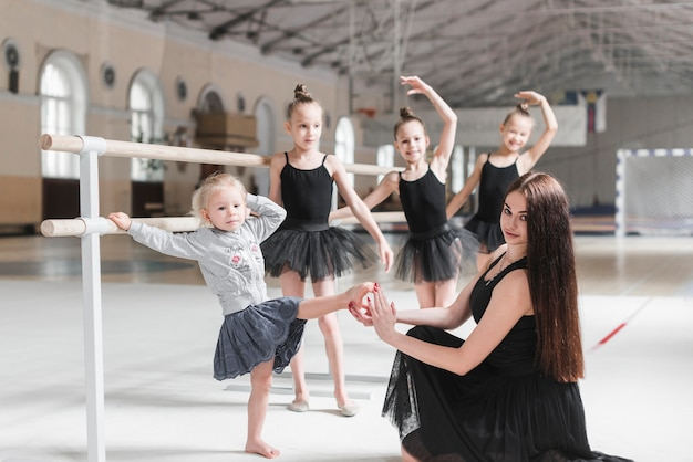 Teacher holding beginner's foot in hand at dance class