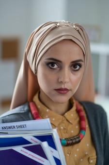 本を持っている先生。学校に立っている本を保持している美しい暗い目のイスラム教徒の教師