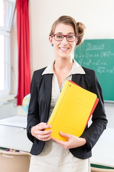 Teacher holding folder in school in front of a class