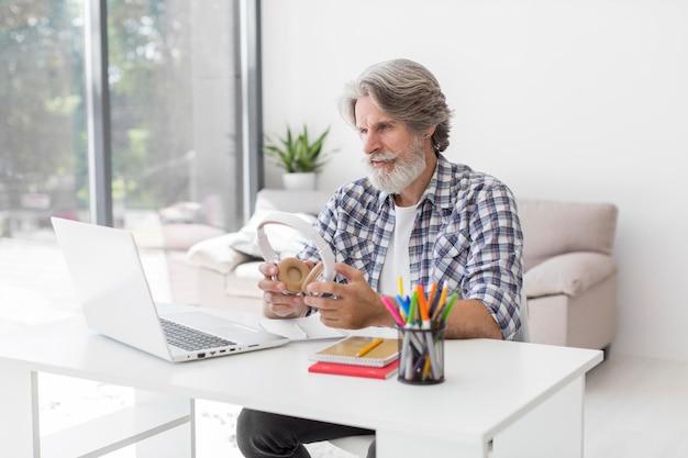 Учитель держит наушники, глядя на ноутбук