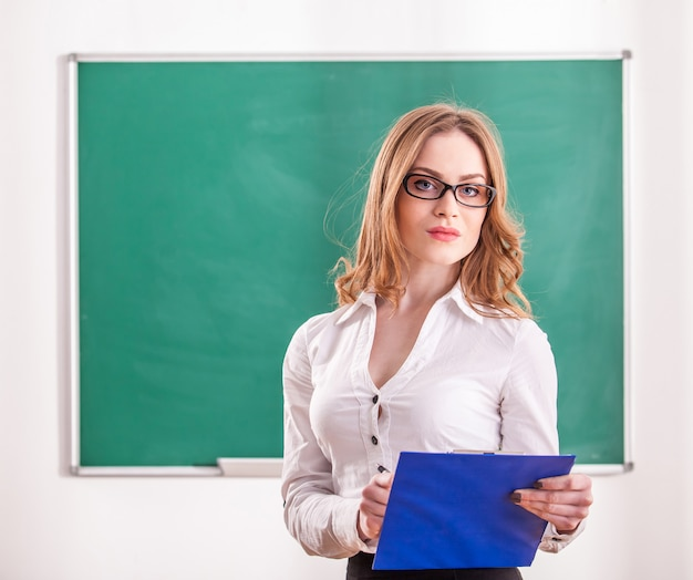 Teacher holding notes in the classroom.